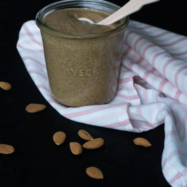 Almond butter in a jar with sprikled almonds 2