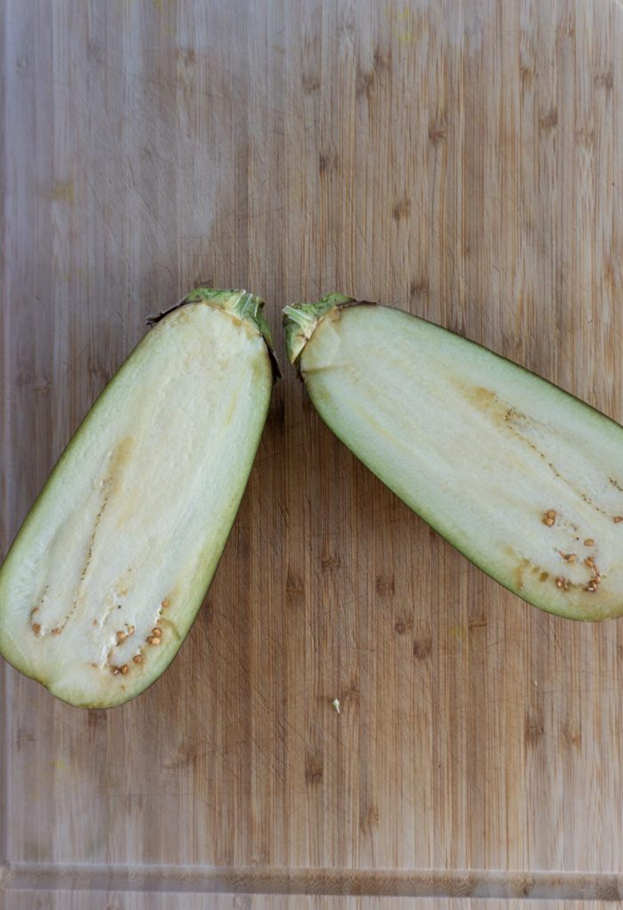 Fresh aubergine cut open on a chopping board