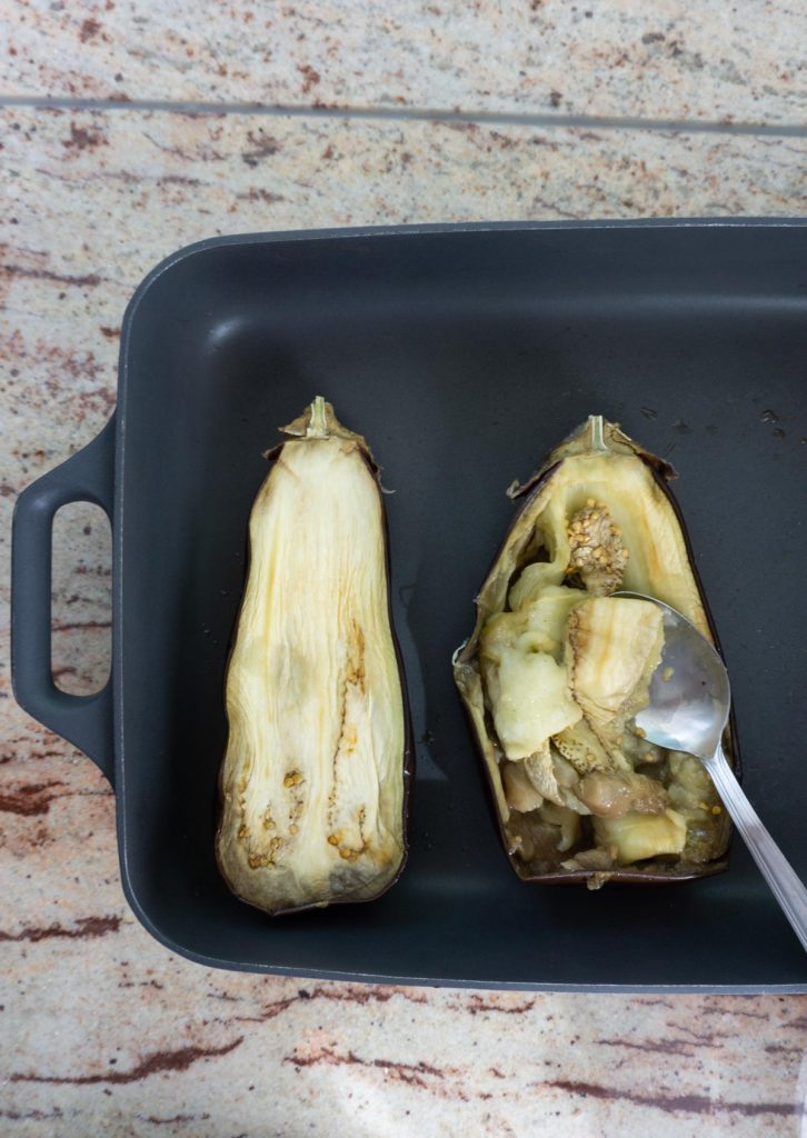 Baked aubergine in a tray being scooped out with a spoon
