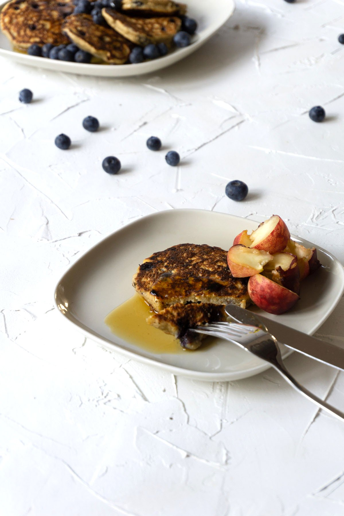 Blueberry Ricotta Pancakes eaten with maple syrup and peaches