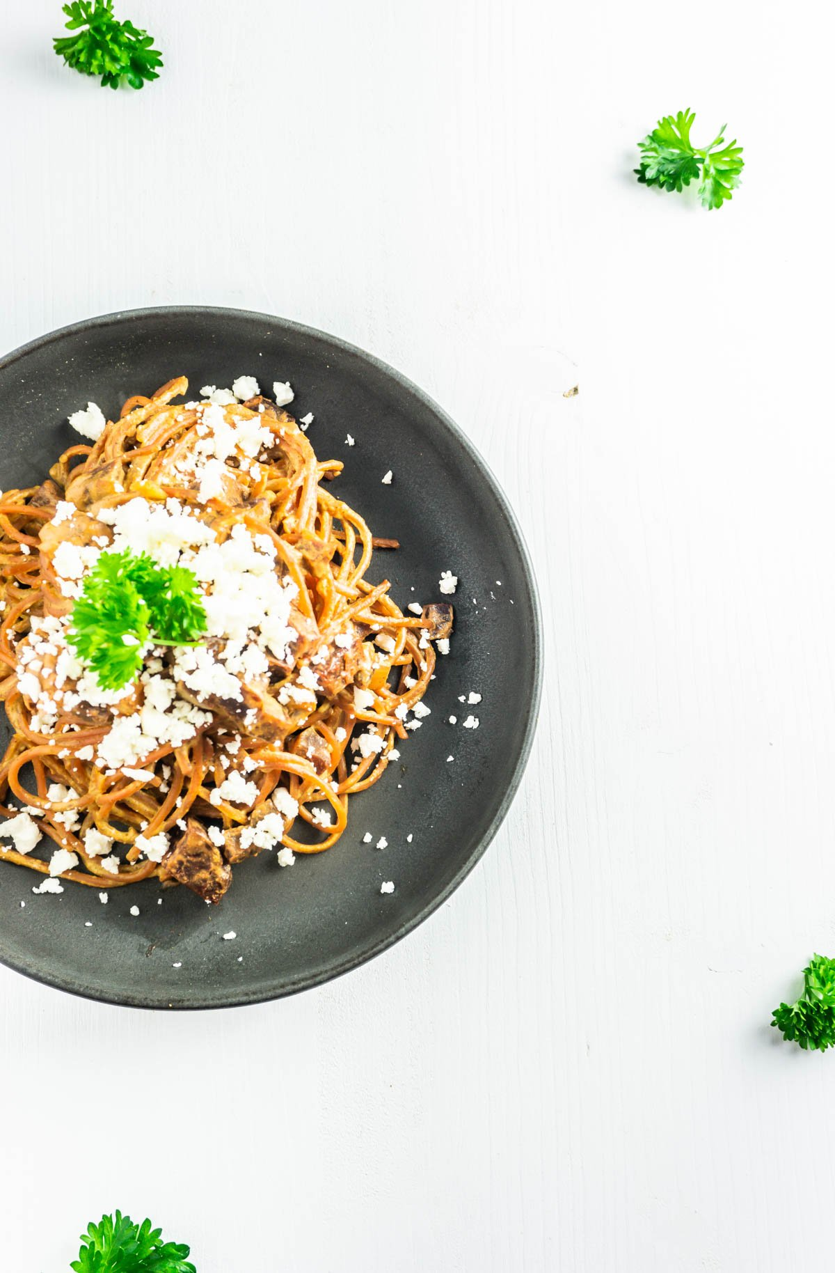 Creamy beetroot pasta on a plate with scattered parsley and feta cheese on top