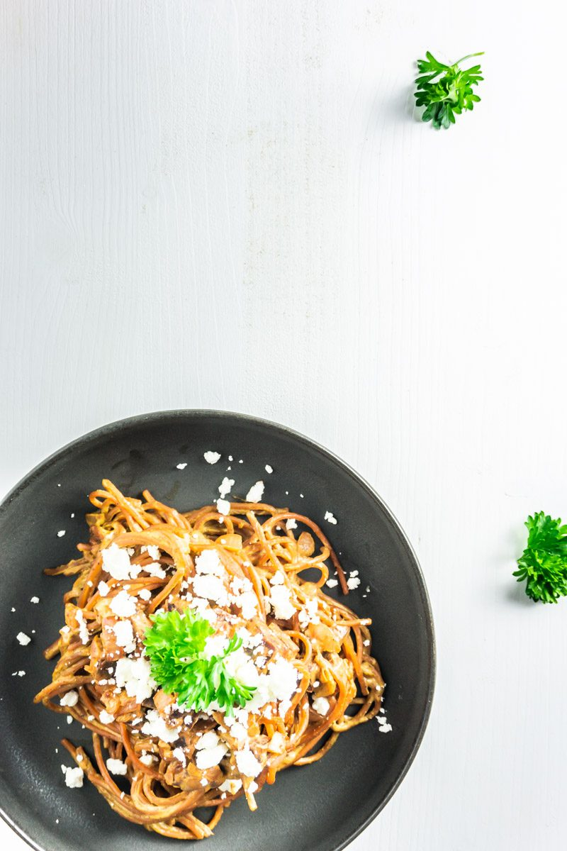 Creamy beetroot pasta on a plate with scattered parsley