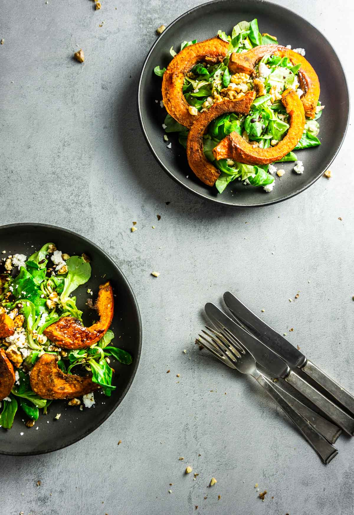 Two plates of baked spiced pumpkin on a bed of lambs lettuce with feta and rocket