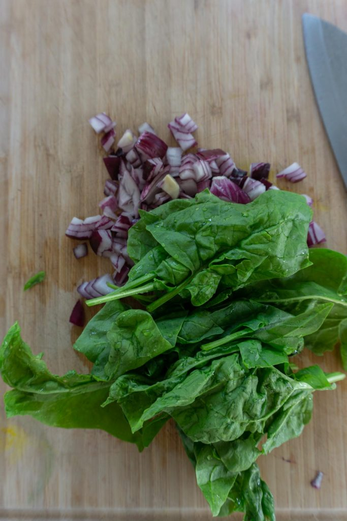 Spinach and chopped red onion on a chopping board