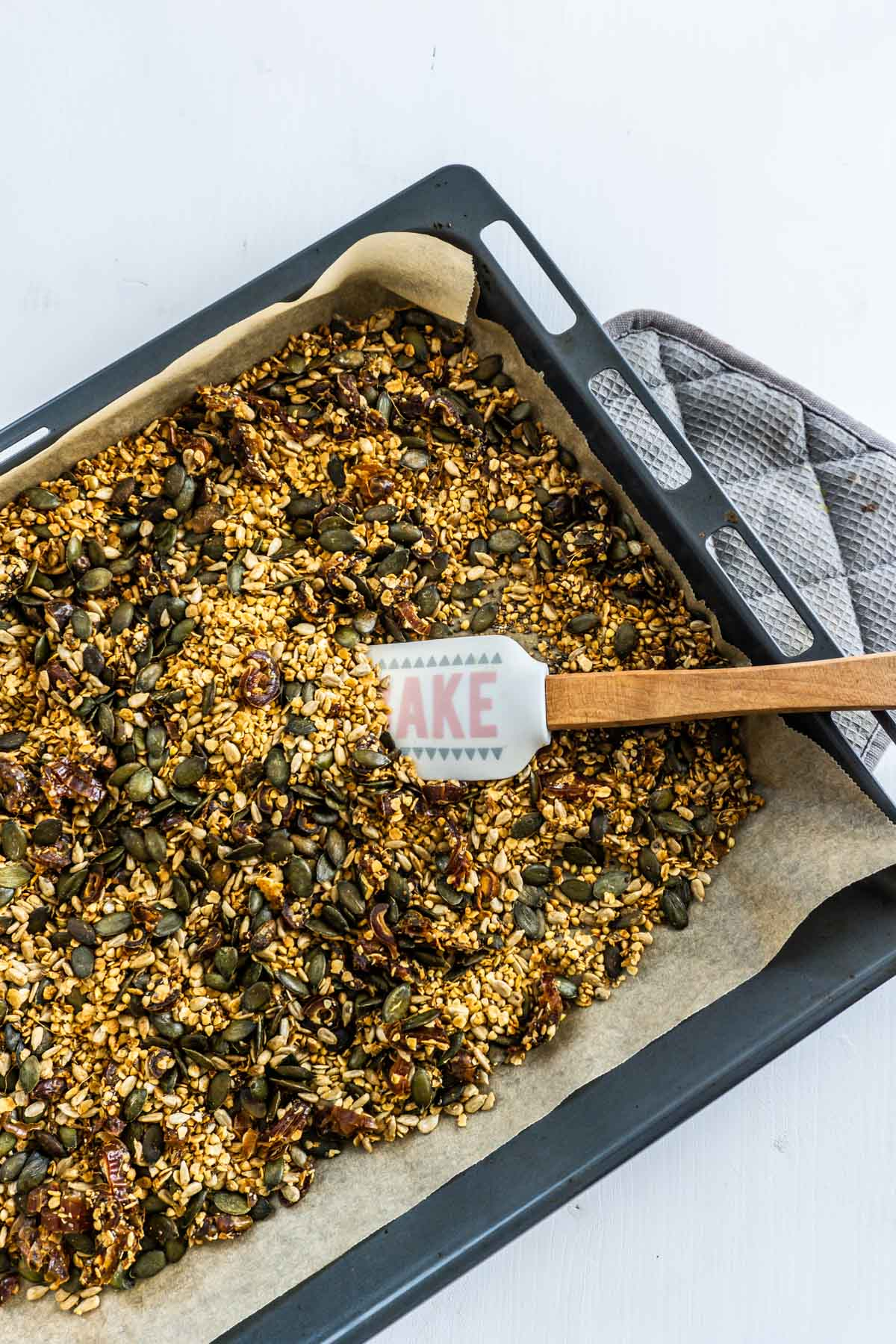 Nut-free ginger granola on a tray with a spatula