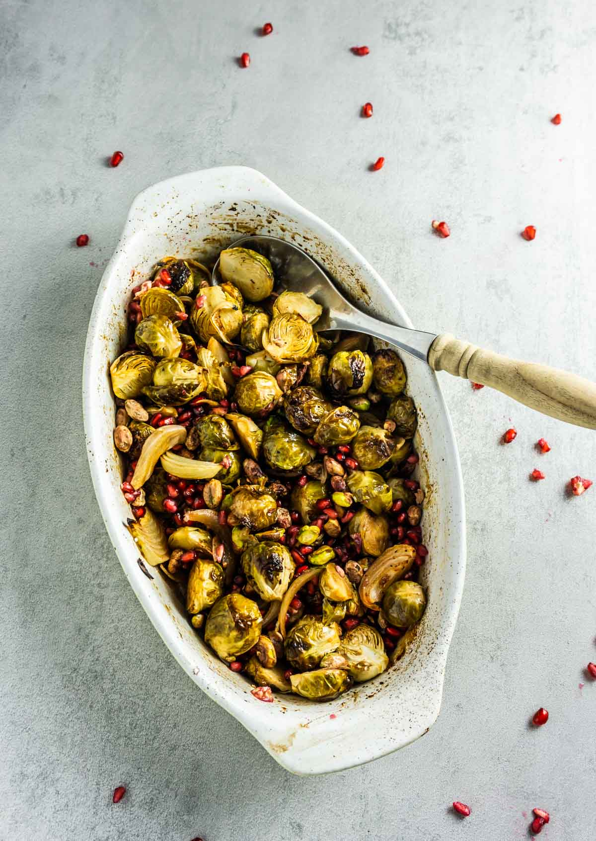 Roasted Brussel sprouts in a pan baking dish with a wooden spatula