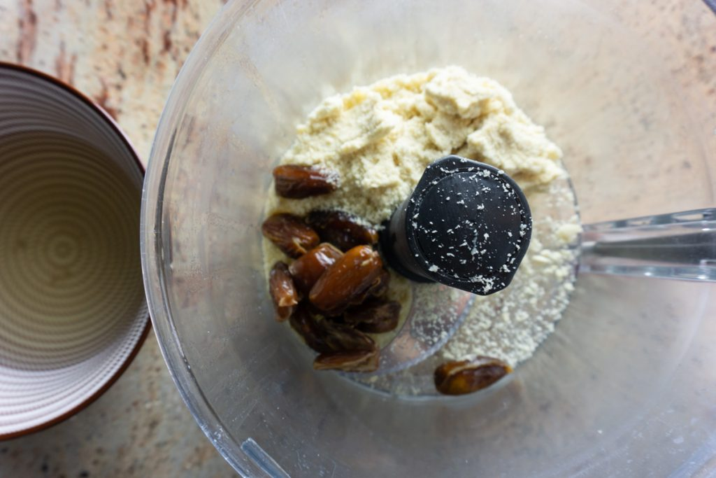 Blanched almond meal and dates in a food processor