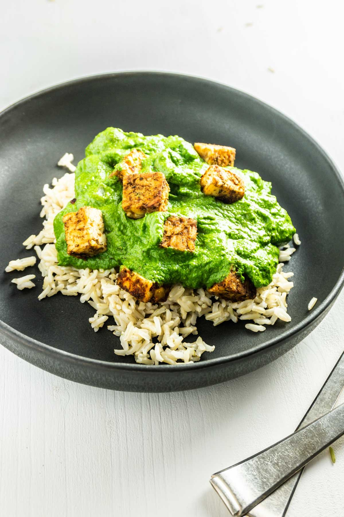 Vegan Palak Paneer on a plate with cutlery