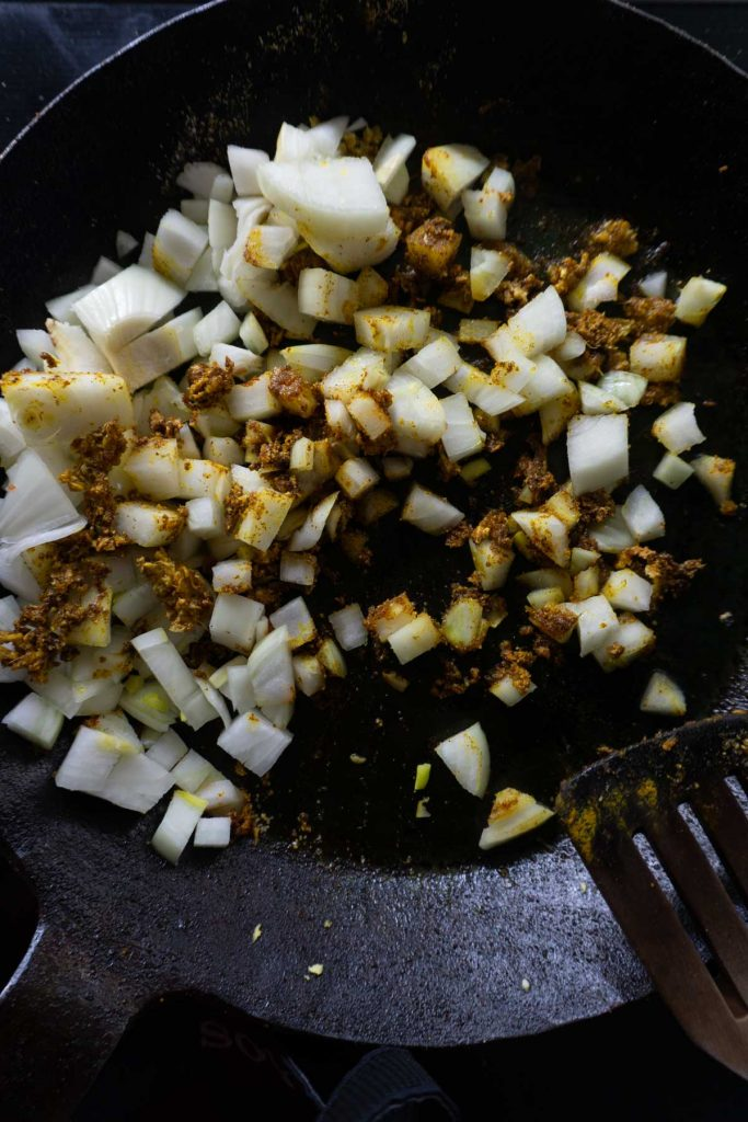Onion with ginger and spices in a pan