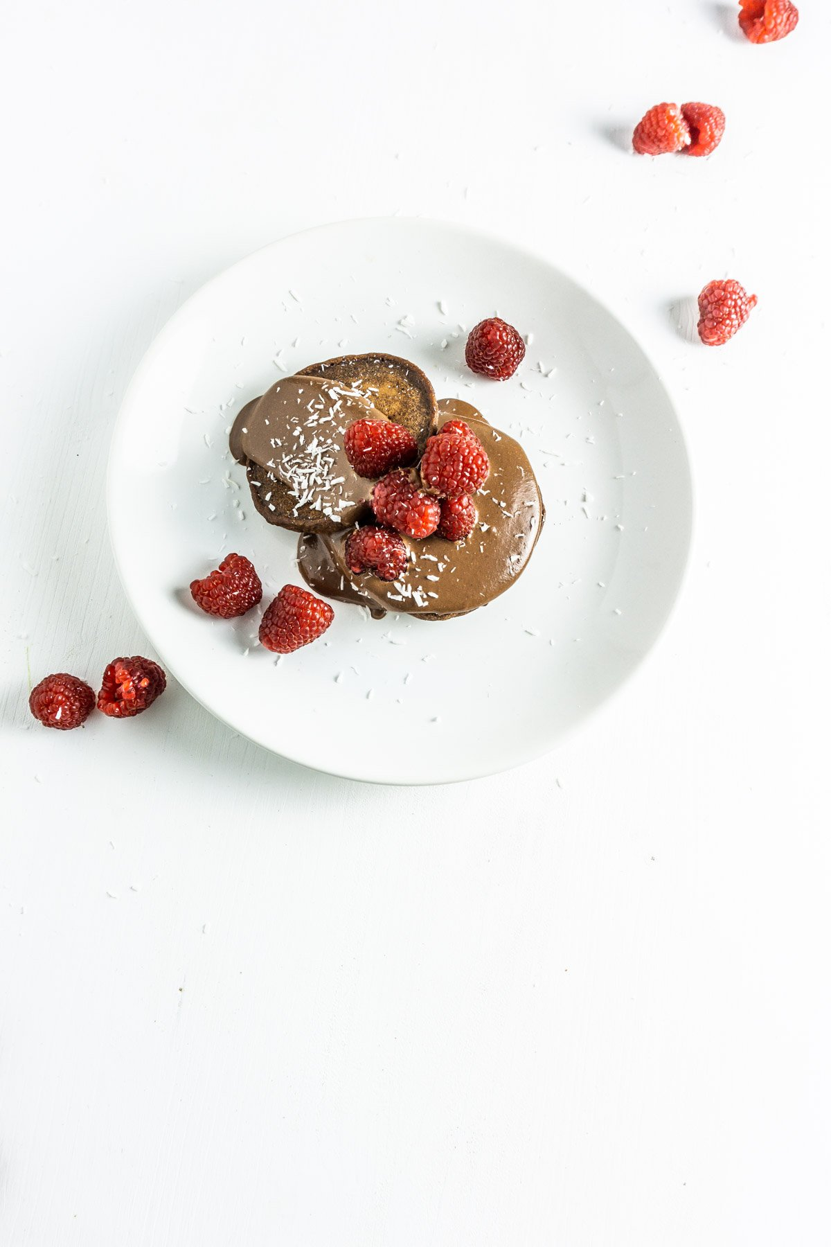 Chocolate banana pancakes with a chocolate and hazelnut sauce on a plate with raspberries
