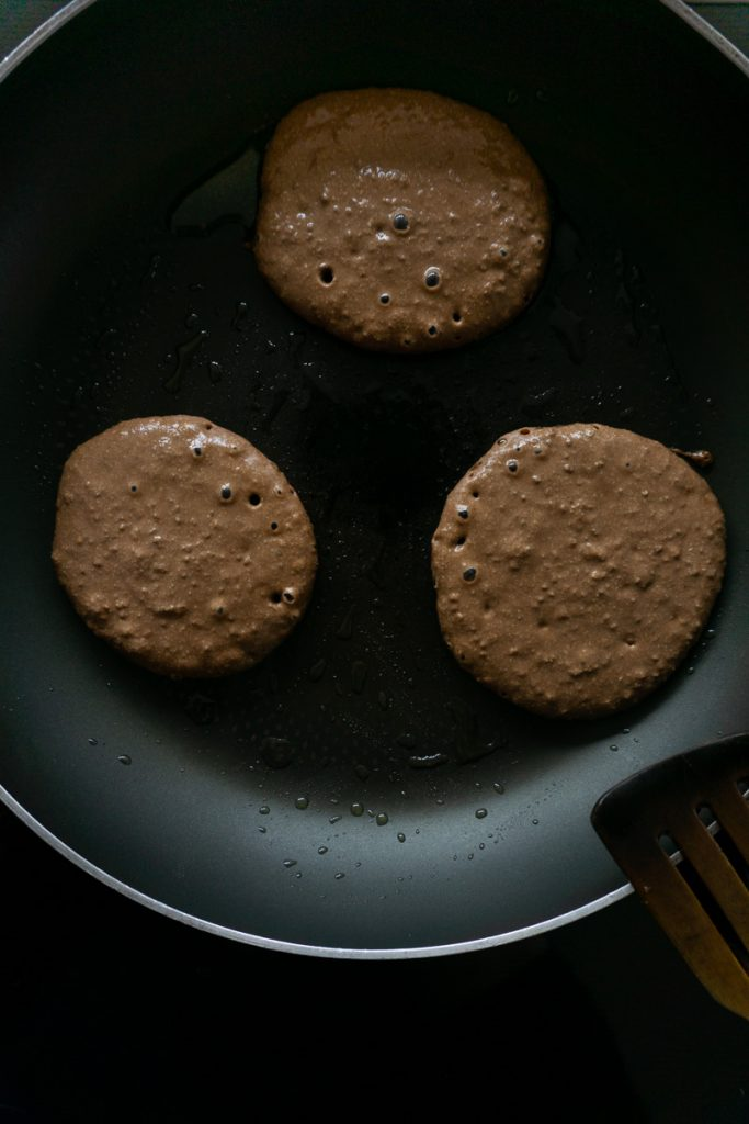 Pancakes in a pan with bubbles developing