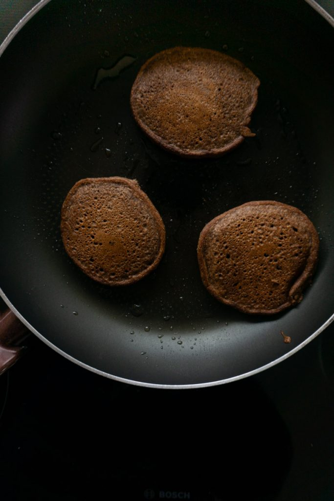 Pancakes in a pan browned on one side