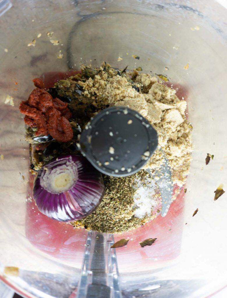 Adding walnut flour, onion, tomato paste, salt, oregano and tamari to eggplant in food processor