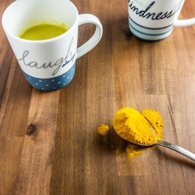 Two cups with golden latte on a wooden surface with turmeric on a spoon