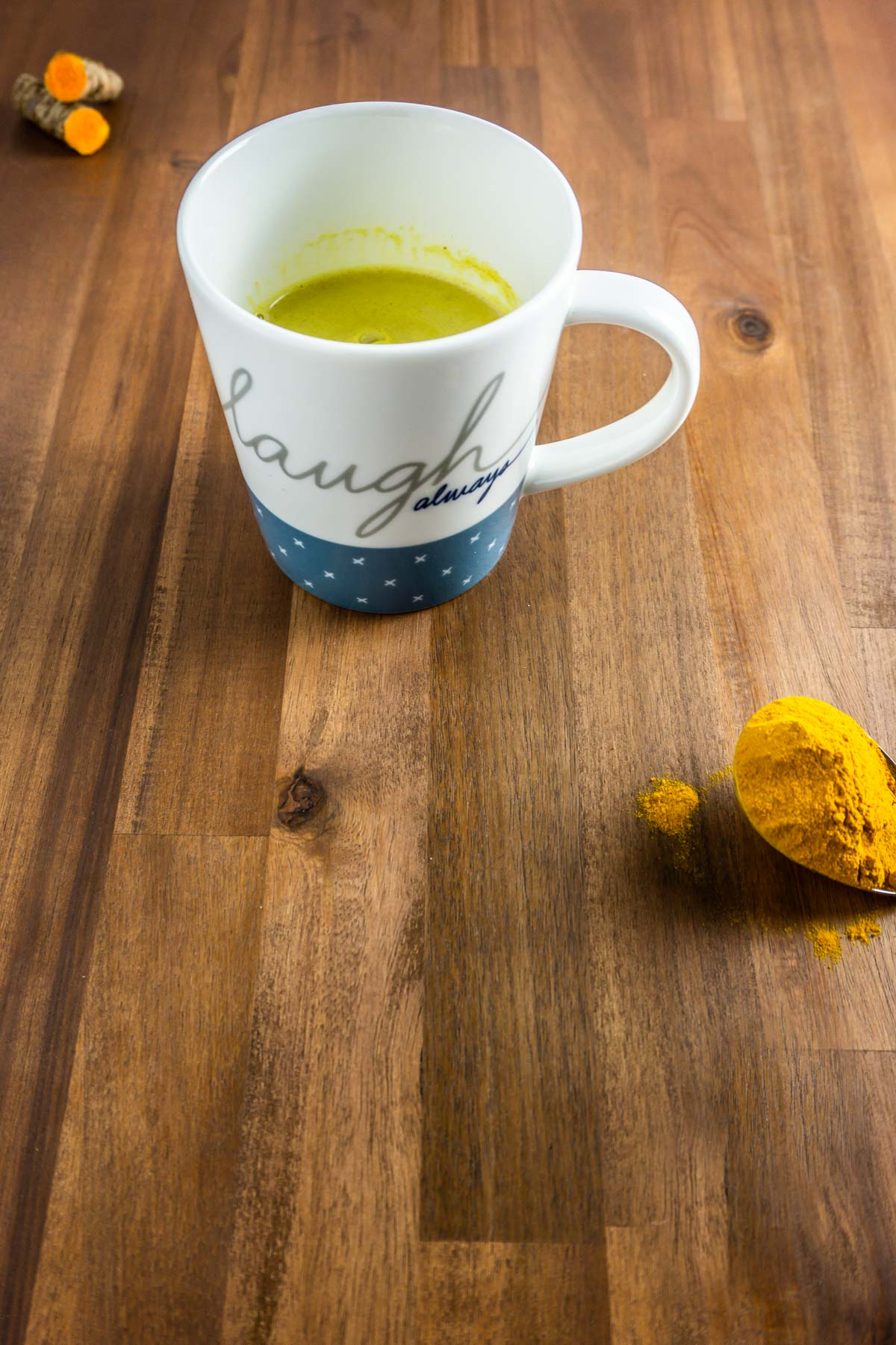 Golden latte on a wooden surface with turmeric on a spoon
