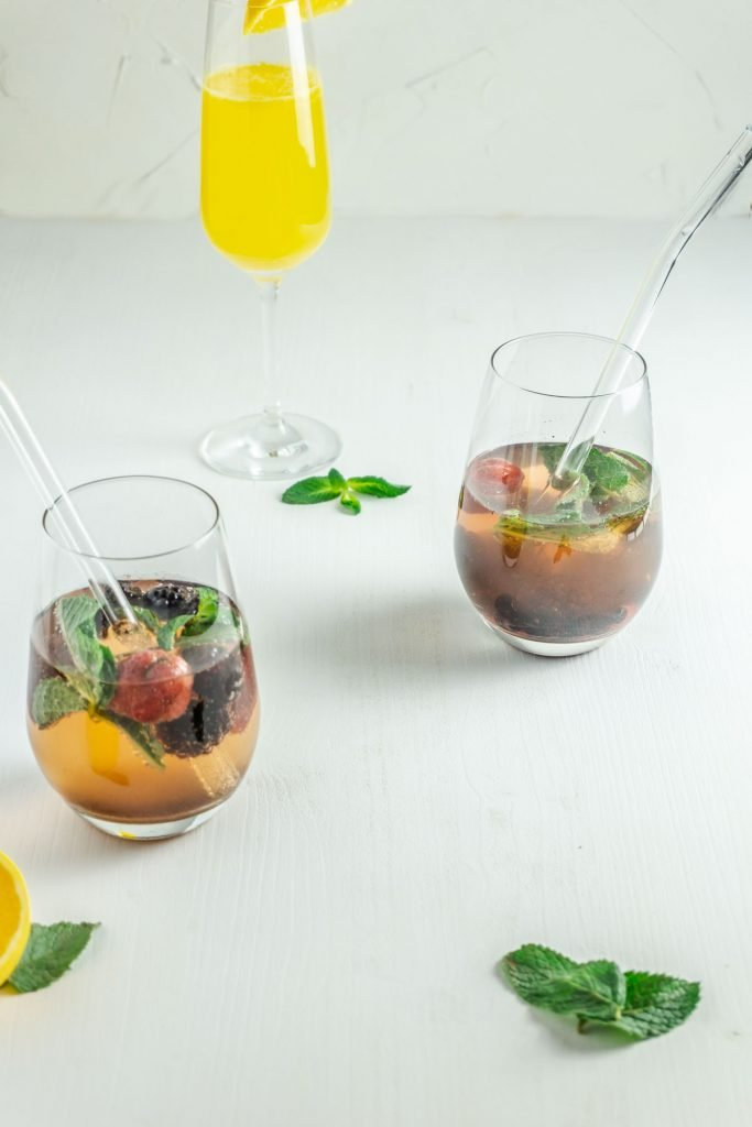 Ginger-Orange and Mint-Berry Mocktail on a white background