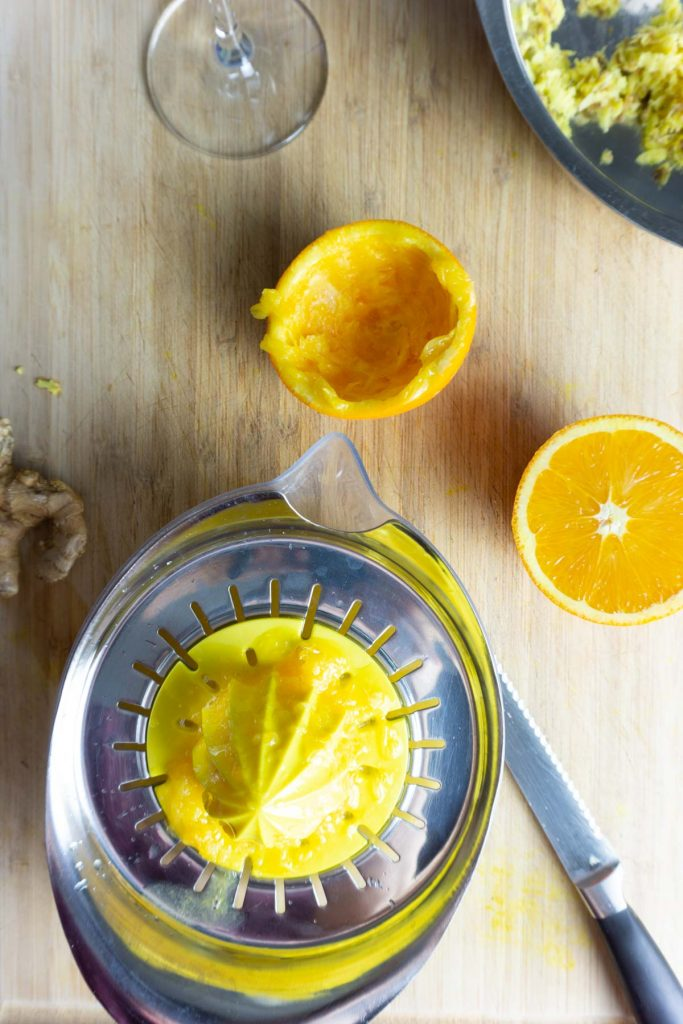 An orange pressed in a juicer