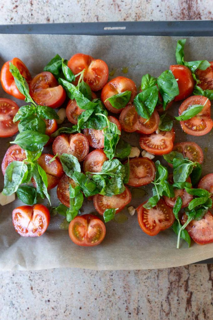 Tomatoes with basil, olive oil, garlic, salt and pepper on a tray