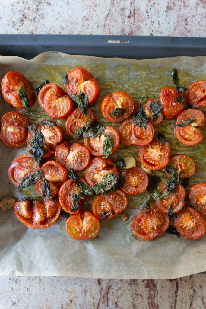 Tomatoes with basil, olive oil, garlic, salt and pepper on a tray after baking