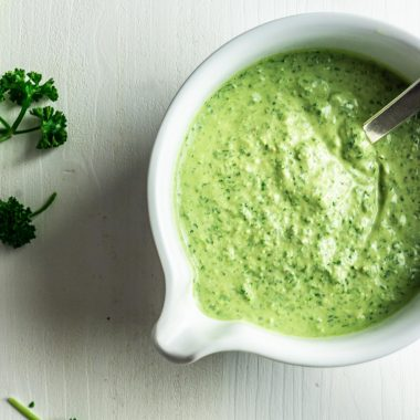 Frankfurter Green Sauce (vegan) on a white background with sprinkled herbs