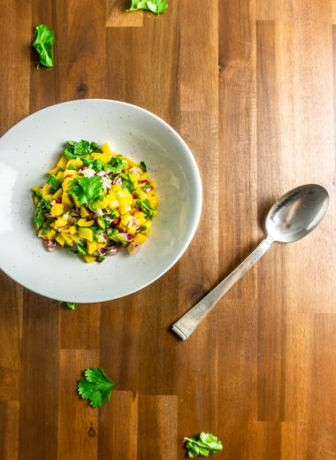 Mango Salsa in a white bowl on a wooden background with a spoon