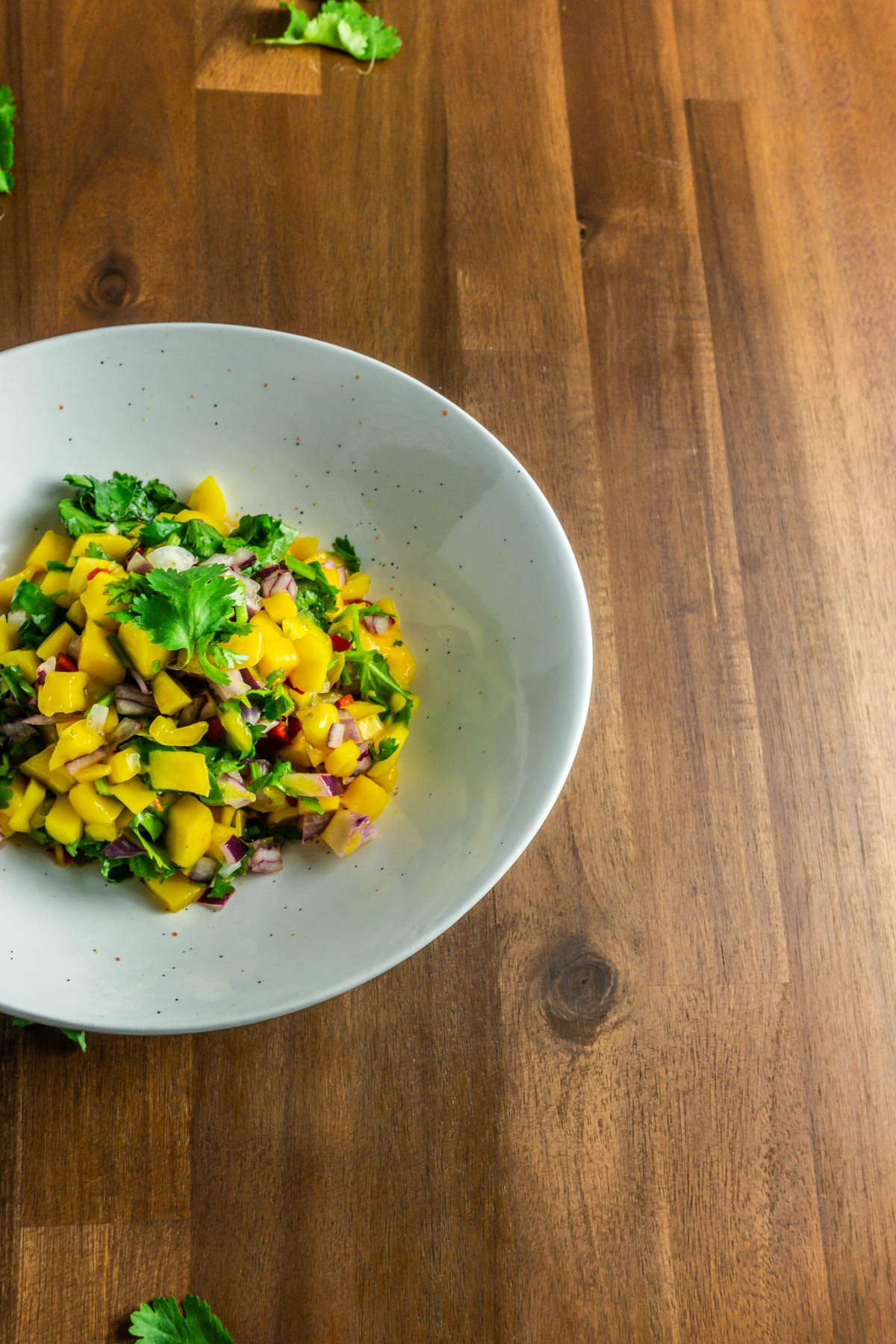 Mango Salsa in a white bowl on a wooden background