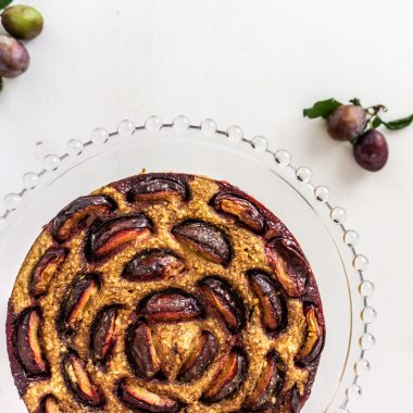 Plum cake on a stand with a white background