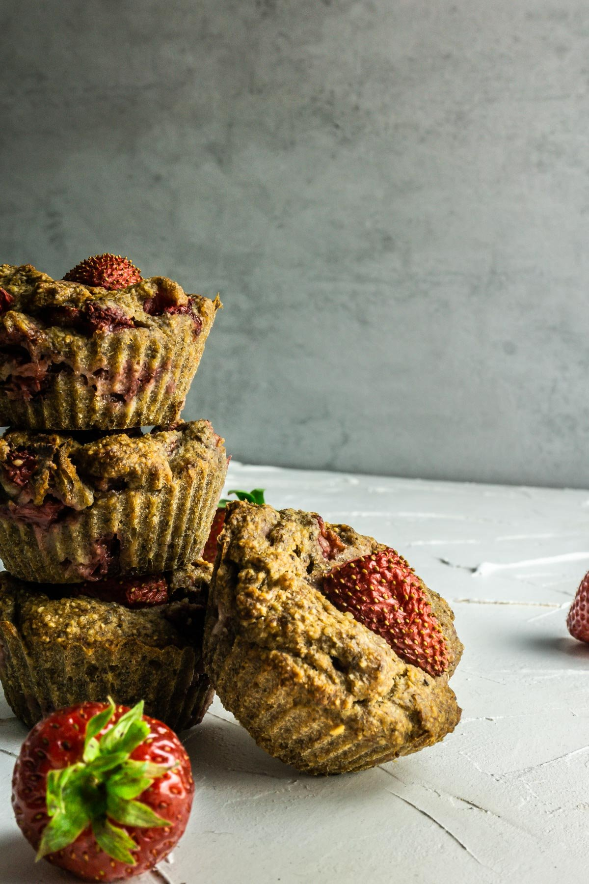 Stacked Strawberry Banana Muffins on a white background