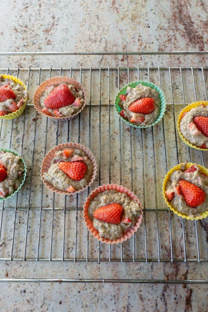 Filling dough into muffin cups with strawberries on