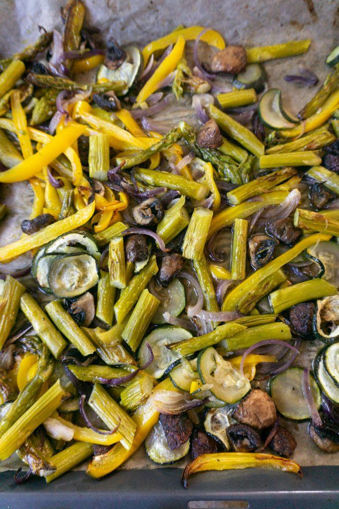 Roasted green asparagus, courgette, onions, mushrooms, and pepper on a baking tray
