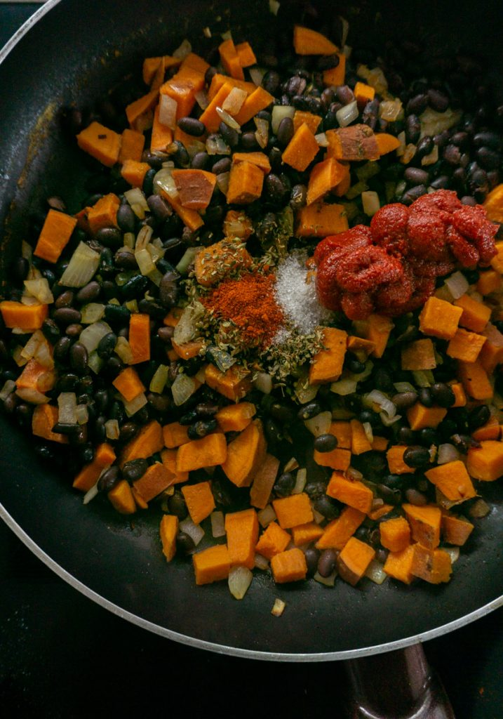 Sweet potato, onions, black beans, spices and tomato paste in a pan