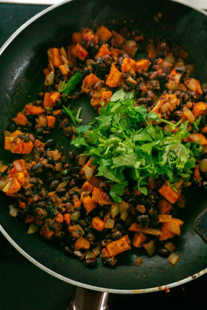Sweet potatoes, onions, black beans, spices, tomato paste and coriander in a pan