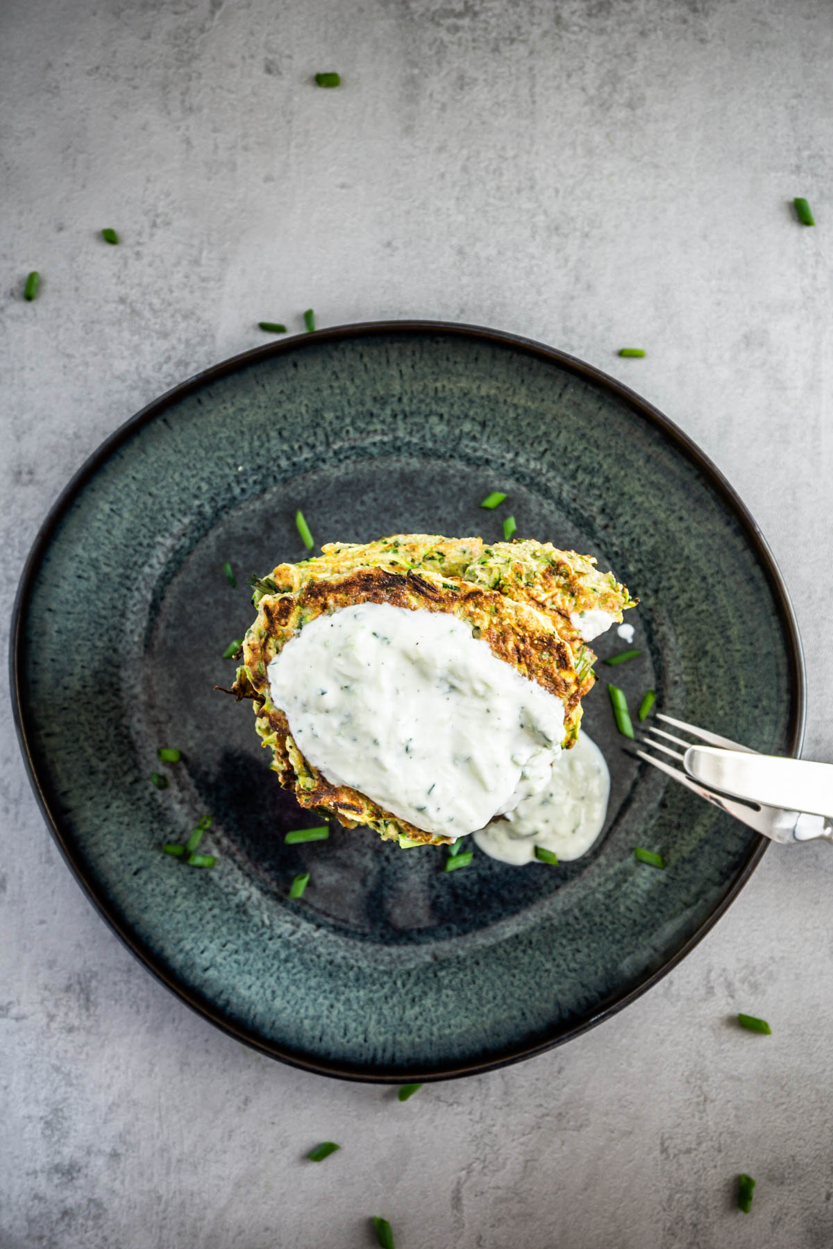 Courgette Fritters on a grey background with yogurt on top