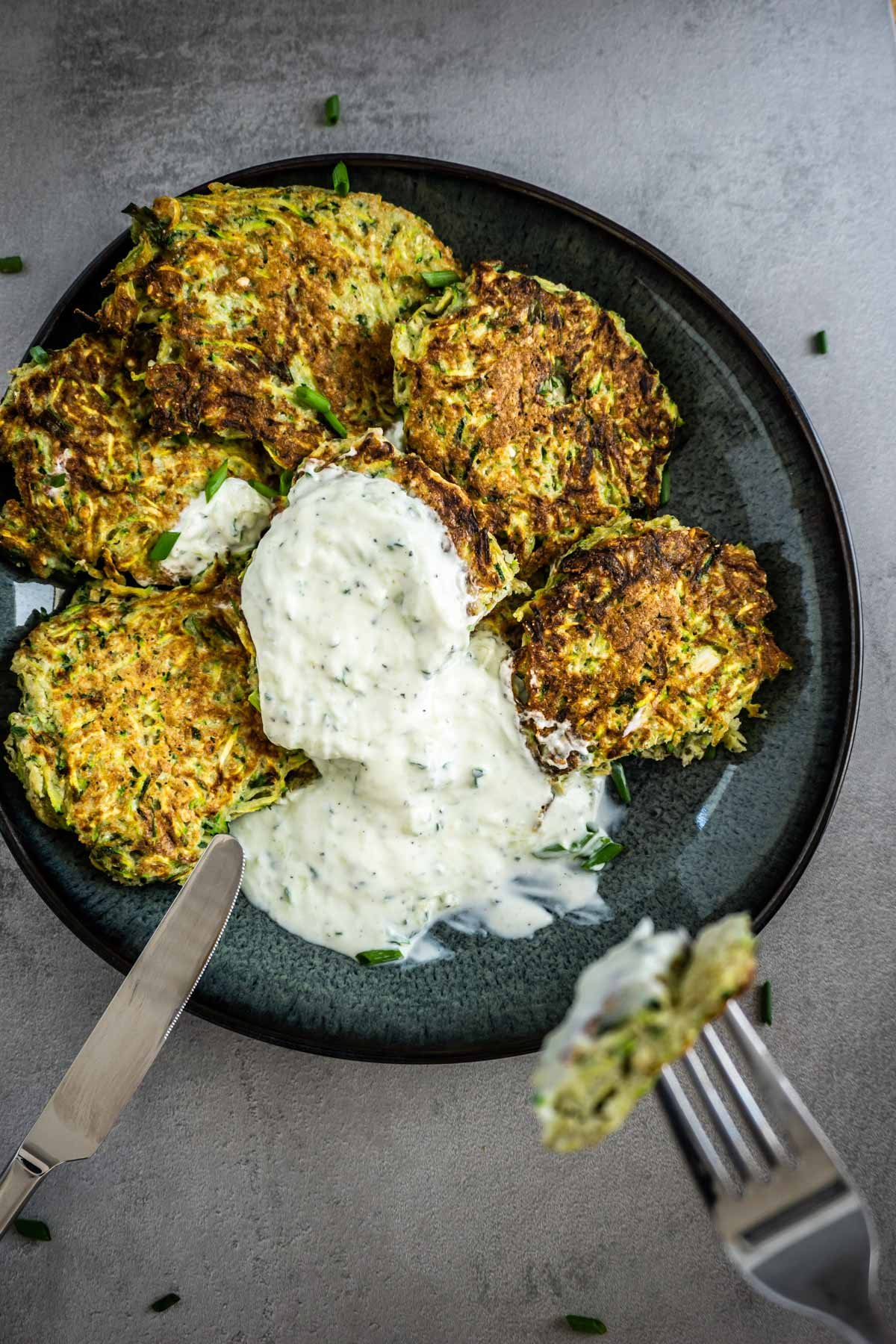 Eating Courgette Fritters on a grey background with yogurt on top