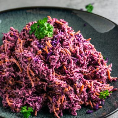 Easy Purple Coleslaw on a dark plate and grey background