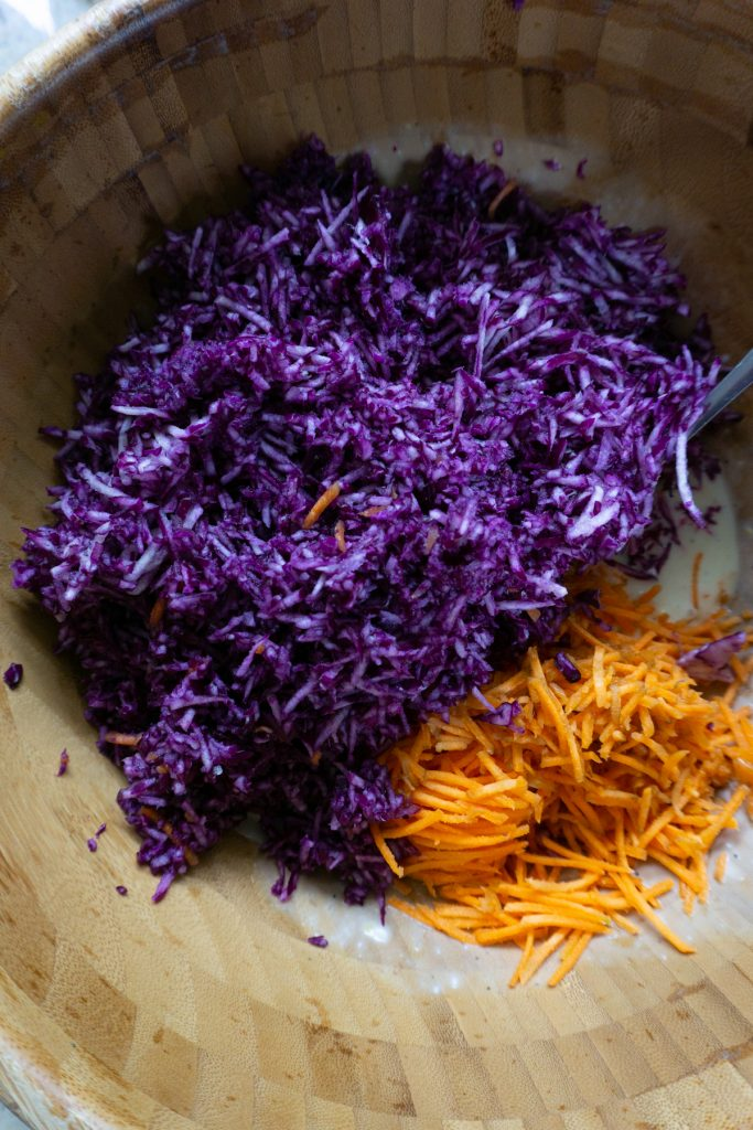 Adding shredded purple cabbage and carrots to coleslaw sauche