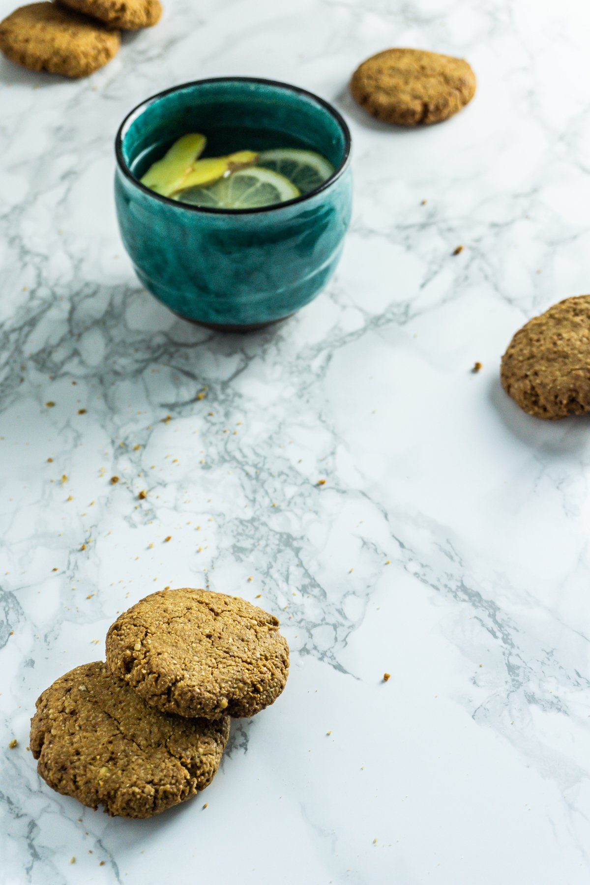Scattered Crunchy Ginger Cookies with a lemon and ginger tea on a marble background