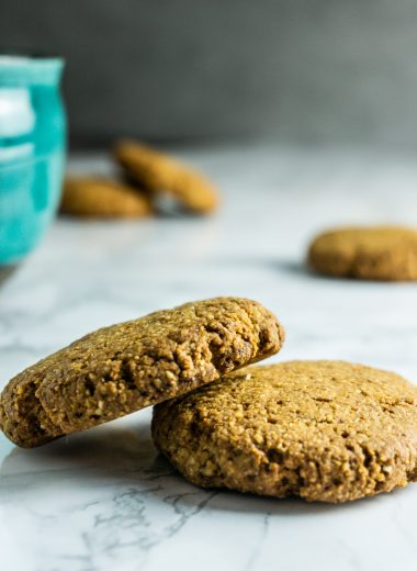 Scattered Crunchy Ginger Cookies with a green cup in the background