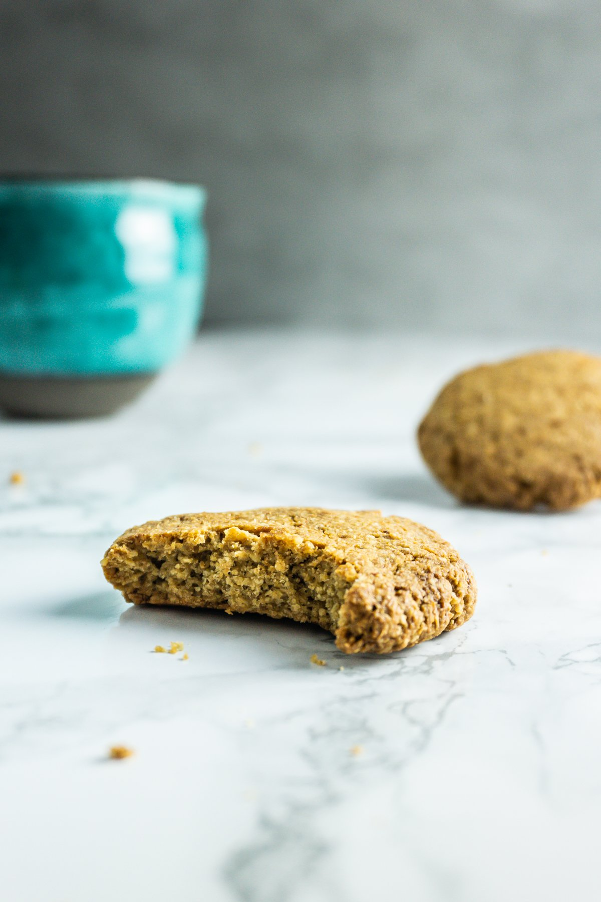 Bitten Crunchy Ginger Cookie with a green cup in the background
