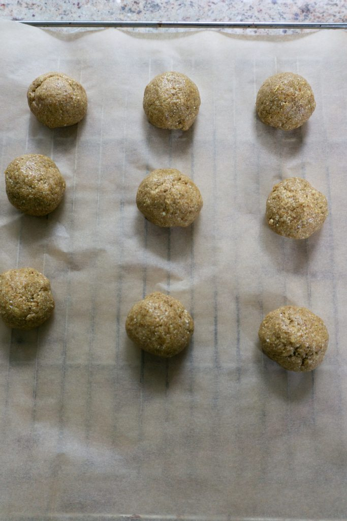 Putting dough in balls on a baking tray with parchment paper