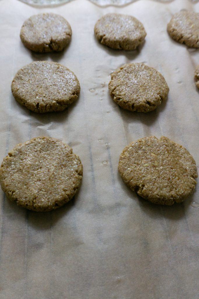 Flattening dough balls into cookie shapes on a baking tray with parchment paper