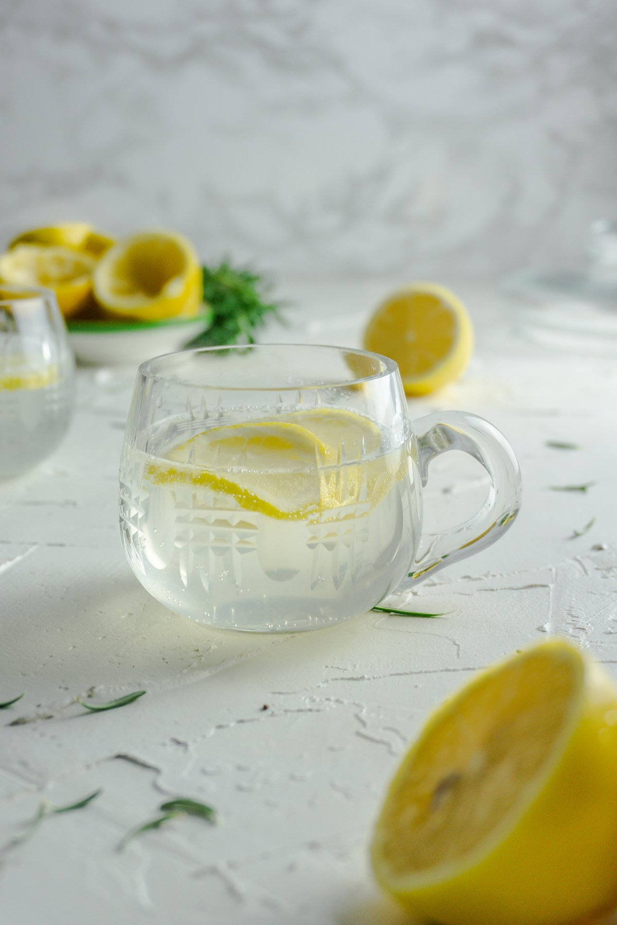 Small cup with Summer Day Lemonade on a white background with strewn rosemary and lemons