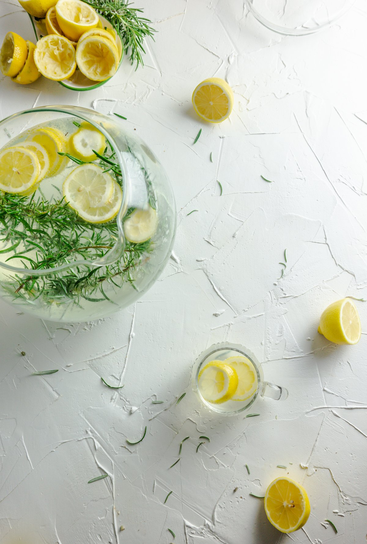 Small cup with Summer Day Lemonade on a white background with strewn rosemary and lemons and a large pitcher photographed from the top