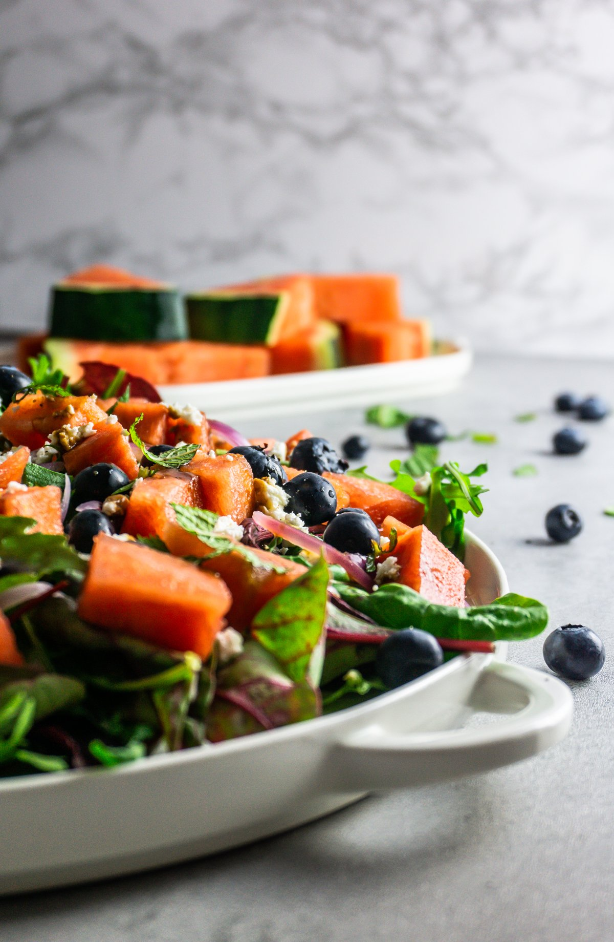 Watermelon Feta Salad on a white plate photographed from the side with blueberries, mint, watermelon in the background