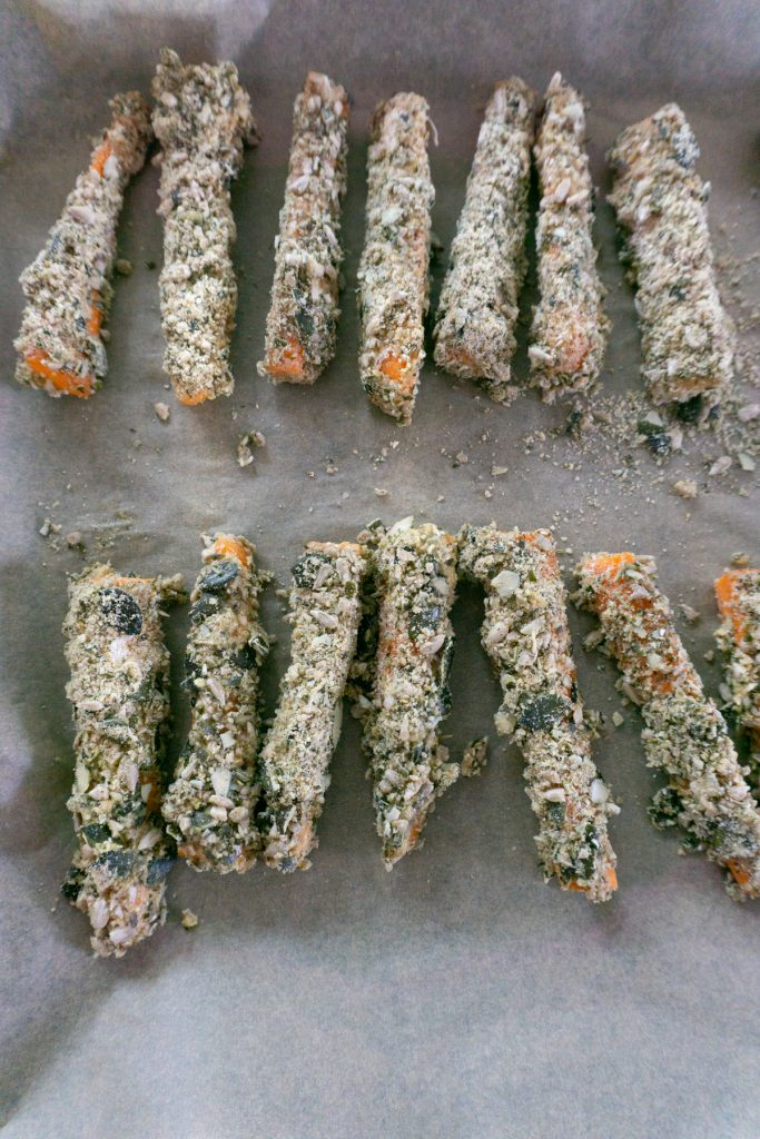 Carrots in crumb mixture on a baking tray