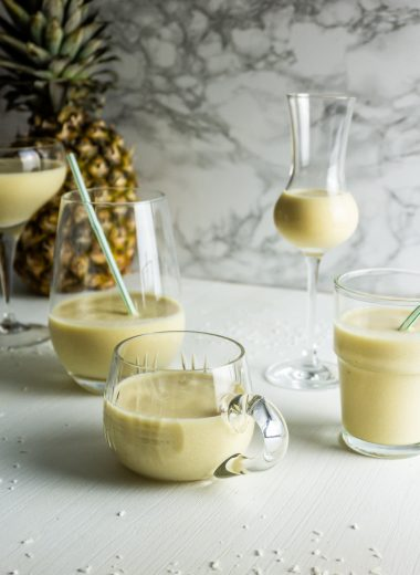 Coconut Pineapple Smoothie in different kinds of glasses on a white background with a pineapple in view