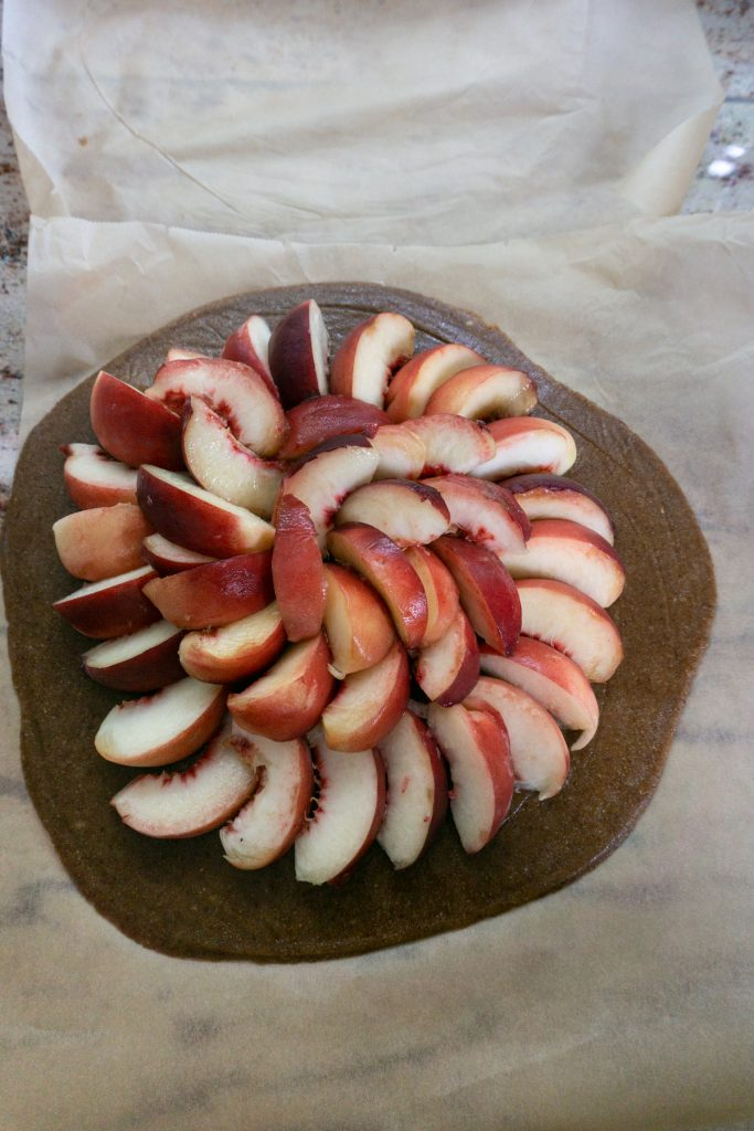Layered peaches in a circular motion on pie crust
