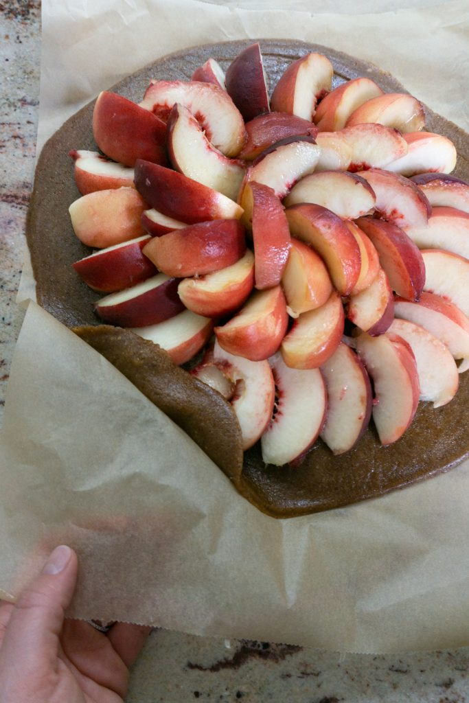 Putting the edges of the pie crust over the peaches