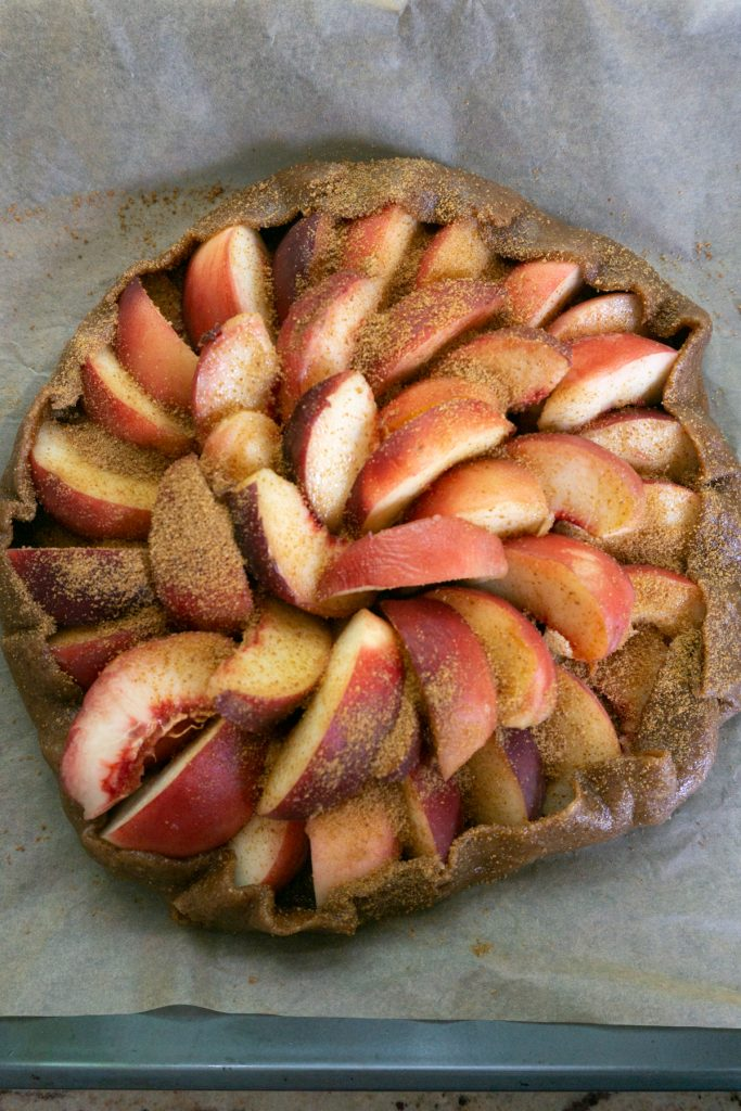 Putting finished Peach Galette on a baking tray and adding coconut sugar on top
