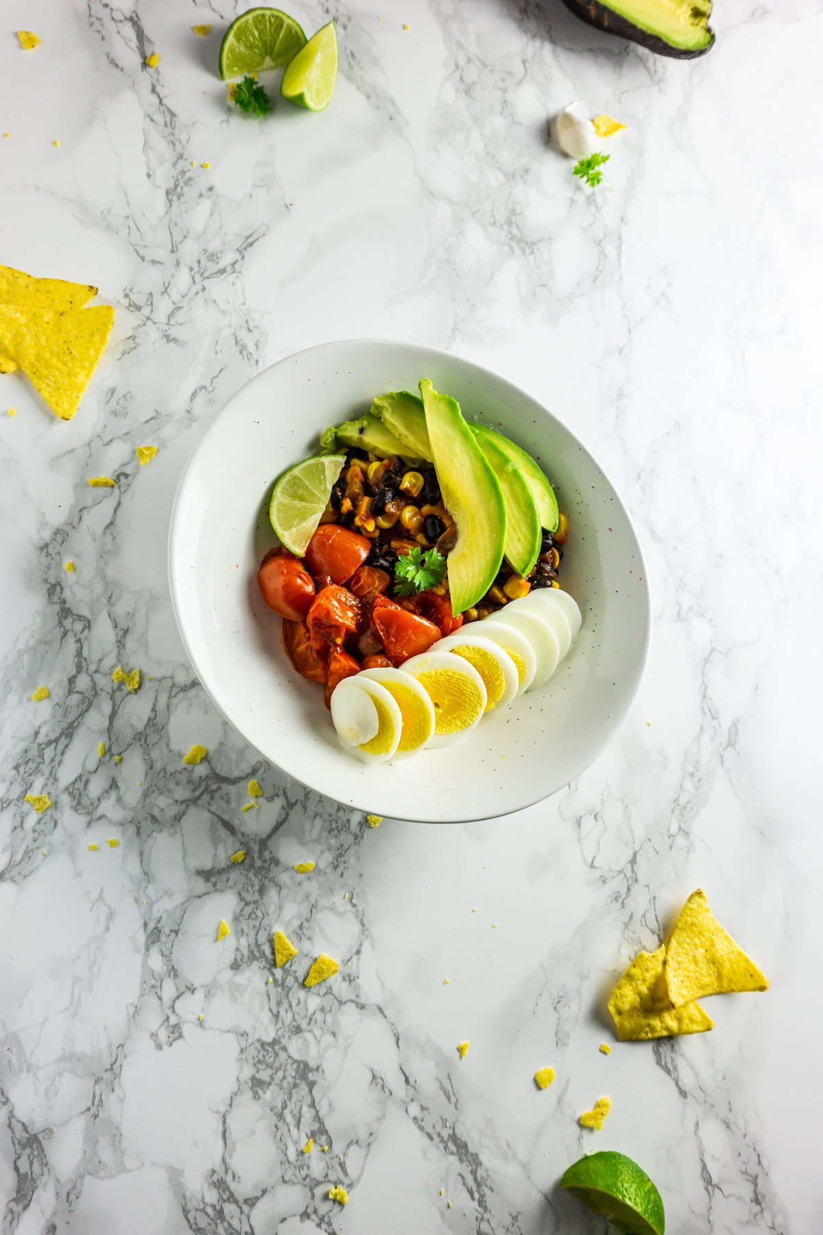 Spicy Breakfast Bowl with nachos, lime, garlic, and avocado photographed on a marble background